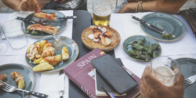Tourists in Barcelona eating tapas in a typical restaurant in the Barri Gotic. On the table a travel guide of Spain and a smartphone.