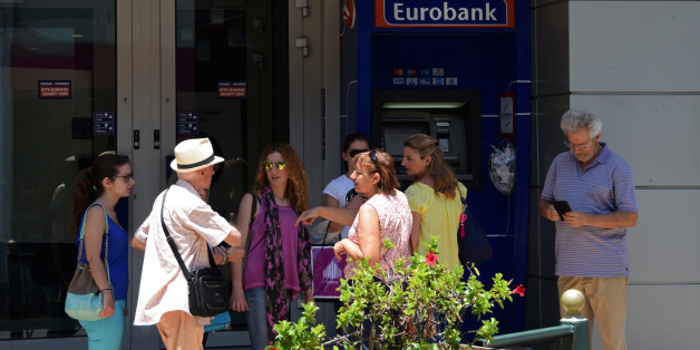Athens, Greece - July 1, 2015: People waiting at atm machine queue outside a closed greek bank inform a tourist that capital controls are not implemented on credit cards issued abroad and there is no daily cash limit for visitors.