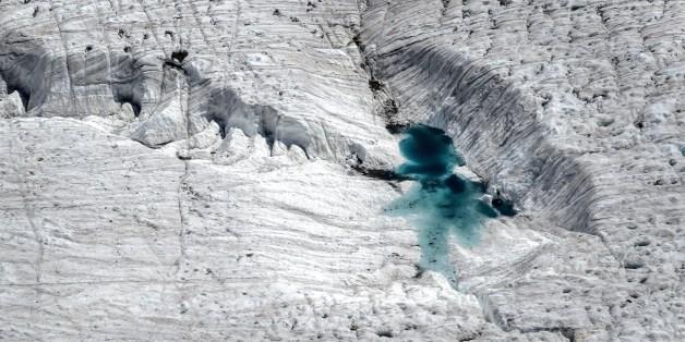A picture shows water on a melting glacier, next to the 3,135 m Gornergrat (Gorner Ridge) above Zermatt, Swiss Alps, on June 30, 2015.   AFP PHOTO / FABRICE COFFRINI        (Photo credit should read FABRICE COFFRINI/AFP/Getty Images)