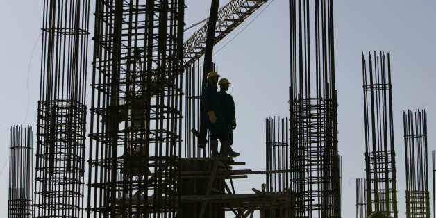 Workers stand on steel reinforcements at a hospital building site during Algeria's President Abdelaziz Bouteflika official visit to the western city of Chlef May 29, 2007.  REUTERS/Zohra Bensemra (ALGERIA)