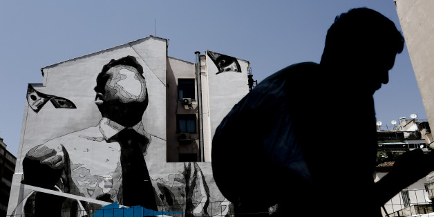 A pedestrian walks past a wall mural by visual artist 'Ino' in Athens, Greece, on Thursday, June 29, 2017. The change in sentiment toward Greece -- the epicenter of the European financial crisis -- is reflected in the fact that countrys bond yields are the lowest since before the turmoil even as the debt remains deep in junk territory. Photographer: Kostas Tsironis/Bloomberg via Getty Images