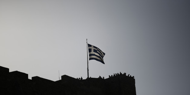 A Greek national flag flies from the top of the Acropolis hill above visiting tourists in Athens, Greece, on Wednesday, June 28, 2017. The change in sentiment toward Greece -- the epicenter of the European financial crisis -- is reflected in the fact that countrys bond yields are the lowest since before the turmoil even as the debt remains deep in junk territory. Photographer: Kostas Tsironis/Bloomberg via Getty Images