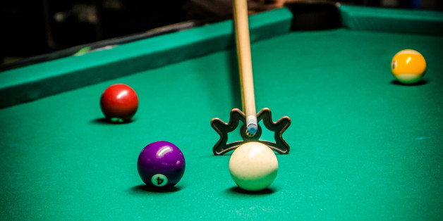 Young and pretty woman using bridge stick to hit cue ball during pool game