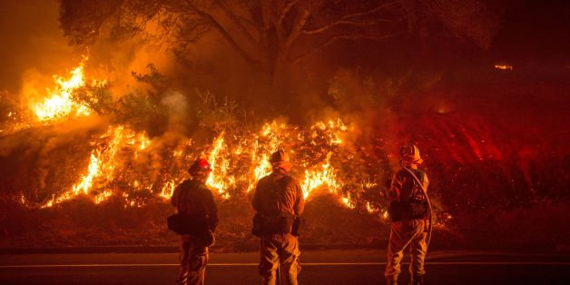 Firefighters monitor flames on the side of a road as the Detwiler fire rages on near the town of Mariposa, California on July 18, 2017. California has suffered widespread fires in recent days, with a lighting strike near Yosemite National Park sparking a blaze that destroyed more than 26 square kilometers (10 square miles) of forest. / AFP PHOTO / JOSH EDELSON        (Photo credit should read JOSH EDELSON/AFP/Getty Images)