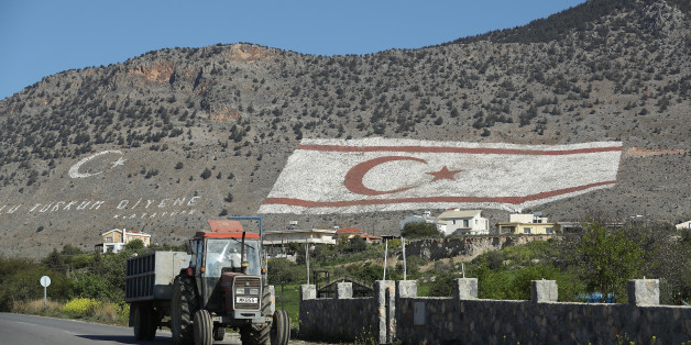 TASKENT, CYPRUS - MARCH 06:  A tractor in the Turkish Republic of North Cyprus (TRNC) drives by a massive TRNC flag that adorns a mountainside on March 6, 2017 in Taskent, Cyprus. Cyprus has been divided into a Greek south and Turkish north ever since the brief but devastating war of 1974. Since then United Nations peacekeepers have maintained a buffer zone that runs through the capital city of Nicosia and across the entire island to keep the factions apart. In the south the Greek-dominated Republic of Cyprus is internationally-recognized and a member of the European Union, while in the north the self-proclaimed Turkish Republic of North Cyprus (TRNC) is recognized only by Turkey, which also has tens of thousands of troops stationed there. Negotiations over possible reunification have made strident progress over the last few years, though they have stalled in recent months.  (Photo by Sean Gallup/Getty Images)