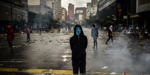 An masked opposition activist takes part in a blockade to protest against Venezuelan President Nicolas Maduro in Caracas, on July 19, 2017.