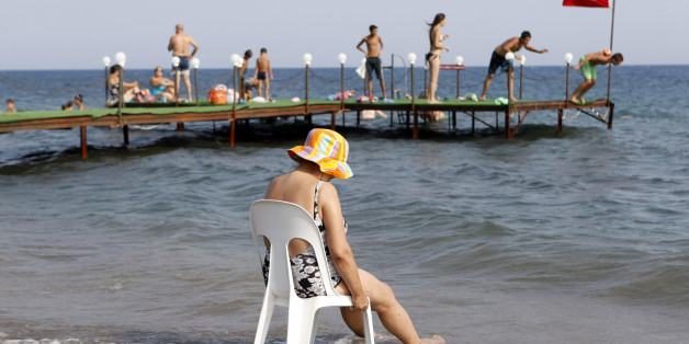 A holidaymaker cools herself at a public beach in the Aegean town of  Kucukkuyu, western Turkey, August 7, 2010. The hot weather across Turkey is expected to last 10 more days as temperatures rise above seasonal norms by 6-8 degrees Celsius in most parts of the country. Picture taken August 7 2010.  REUTERS/Murad Sezer (TURKEY - Tags: SOCIETY ENVIRONMENT TRAVEL)