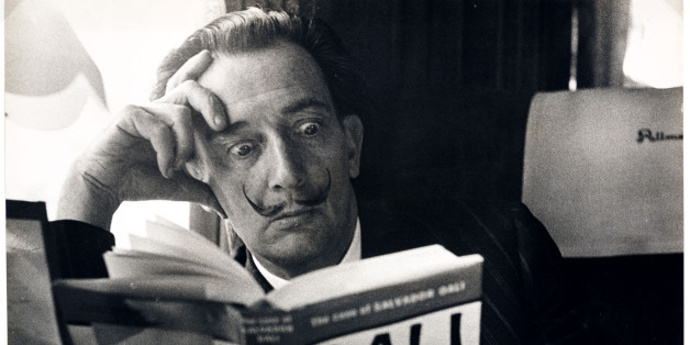UNITED KINGDOM - NOVEMBER 21:  Salvador Dali reading his biography, 6 May, 1959. A photograph of the Spanish artist Salvador Dali (1904-1989), taken by Terry Fincher for the Daily Herald newspaper. Dali is reading Fleur Cowles' book 'The Case of Salvador Dali' (1959), whilst on a train from Folkestone, having travelled from France. Cowles' book was an authorised biography of Dali. With a studied expression of shock on his face, Dali enjoys the photo opportunity. One of the most famous, charismat