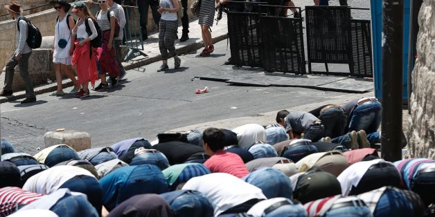 Israeli security forces stand guard as Palestinian Muslim worshippers pray outside Lions' Gate, a main entrance to the Al-Aqsa mosque compound in Jerusalem's Old City, on July 22, 2017, in protest against new Israeli security measures implemented at the holy site following an attack that killed two Israeli policemen the previous week.Stabbings and clashes that left six people dead raised fears of further Israeli-Palestinian violence as tensions mount over new security measures at the highly sens