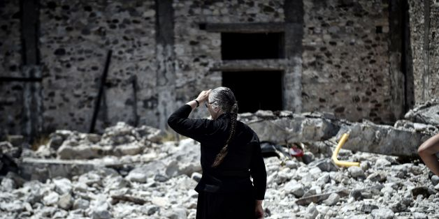 A woman looks at quake-damaged buildings on the Greek Island of Kos on July 22, 2017 , a day after a 6.5 magnitude earthquake struck the region. 