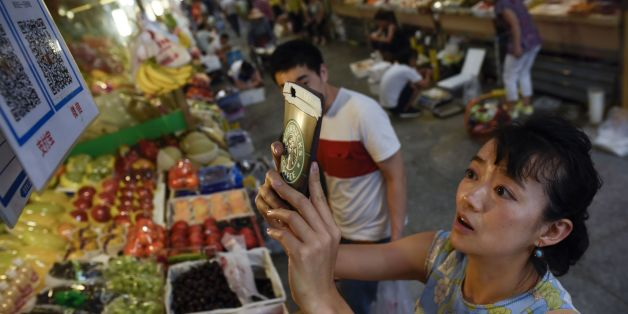 This photo taken on June 27, 2017 shows a woman making purchases by scanning QR codes using her smartphone at a fruit stall in a market in Beijing.China was the first country in the world to use paper money but centuries later the soaring popularity of mobile payment has some analysts forecasting it could be the first to stop.  / AFP PHOTO / WANG ZHAO / TO GO WITH China economy internet, FOCUS by Allison JACKSON        (Photo credit should read WANG ZHAO/AFP/Getty Images)