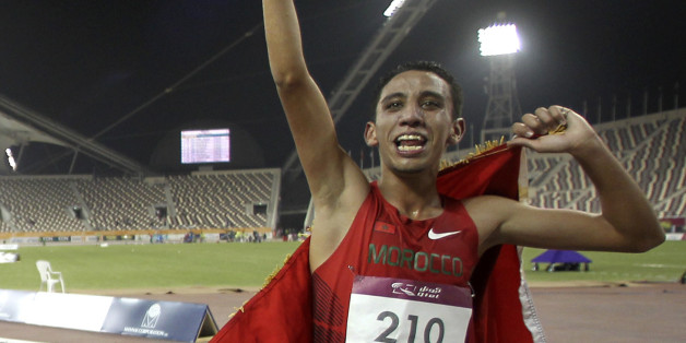 Gold medallist Qatar's Abubaker Ali Kamal (L) and silver medallist Morocco's Soufian Bouqantar celebrate after the men's 5000m final at the 2011 Arab Games in Doha December 20, 2011. REUTERS/Mohammed Dabbous (QATAR - Tags: SPORT ATHLETICS)