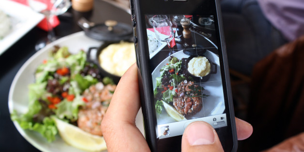 A man takes a picture with his mobile of foods in his plate as he is having lunch on July 19, 2012 in Paris.  AFP PHOTO / ANA AREVALO        (Photo credit should read ANA AREVALO/AFP/Getty Images)