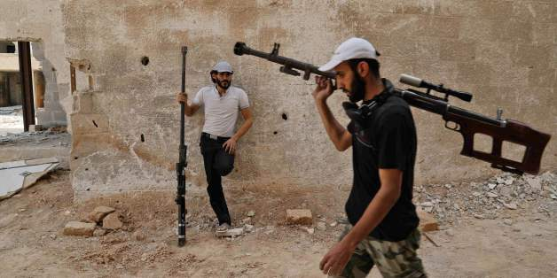 TOPSHOT - Syrian rebel fighters from the Faylaq al-Rahman brigade carry their homemade 12.7mm sniper rifle in Ain Tarma, in the eastern Ghouta area, a rebel stronghold east of the capital Damascus, on July 20, 2017.  / AFP PHOTO / ABDULMONAM EASSA        (Photo credit should read ABDULMONAM EASSA/AFP/Getty Images)