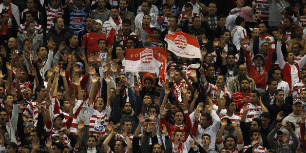 Fans of Tunisia's Club Africain celebrate their team's goal against Morocco's MAS during the first leg soccer match of their Confederation Cup final at Rades Olympic stadium in Tunis November 19, 2011. REUTERS/Zoubeir Souissi  (TUNISIA - Tags: SPORT SOCCER)