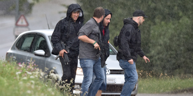 Police officers walk under heavy rain during the hunting in Uhwiesen northern Switzerland, of a man armed with a chainsaw who injured at least five people in Schaffhausen on July 24, 2017.