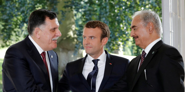 French President Emmanuel Macron stands between Libyan Prime Minister Fayez al-Sarraj (L), and General Khalifa Haftar (R), commander in the Libyan National Army (LNA), who shake hands after talks over a political deal to help end Libya's crisis in La Celle-Saint-Cloud near Paris, France, July 25, 2017.  REUTERS/Philippe Wojazer     TPX IMAGES OF THE DAY