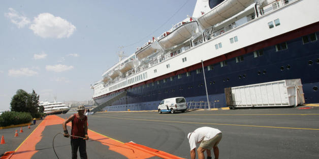 ATHENS, GREECE:  Workers are seen painting an Olympic lane along the 'Ocean Countess' cruiseship that is docked at the Peiraias main port, near Athens City, 03 August 2004. The cruiseship arrived in the port to host some of members of the Olympic family, VIP, and  the media.                 AFP PHOTO / Fayez NURELDINE  (Photo credit should read FAYEZ NURELDINE/AFP/Getty Images)