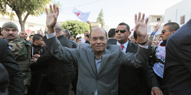 Tunisia's President Moncef Marzouki, who is seeking re-election, greets supporters during a presidential electoral campaign rally at Hai al Tadamon in Tunis November 18, 2014. The Tunisian presidential election is scheduled to be held on November 23. REUTERS/Anis Mili (TUNISIA - Tags: ELECTIONS POLITICS)