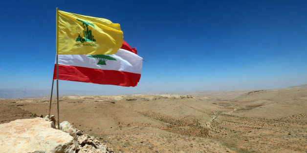 The national flag of Lebanon and the flag of Lebanese Shiite movement Hezbollah are seen placed amidst rocks during a press tour organised by Hezbollah in a mountainous area around the Lebanese border town of Arsal on July 25, 2017.Lebanese movement Hezbollah said its fight against militant groups along the eastern border with war-ravaged Syria was 'nearing its end', and called on fighters to surrender.  / AFP PHOTO / STRINGER        (Photo credit should read STRINGER/AFP/Getty Images)