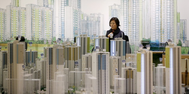 A visitor looks at a miniature model of an apartment complex which is currently under construction at its showroom in Seoul March 18, 2015. While activity is soaring, with the number of transactions at a 7-year high, housing prices are rising at a glacial pace as heavy household debt and a fast-ageing population keep a lid on price growth. To match story SOUTHKOREA-ECONOMY/HOUSING Picture taken on March 18. REUTERS/Kim Hong-Ji