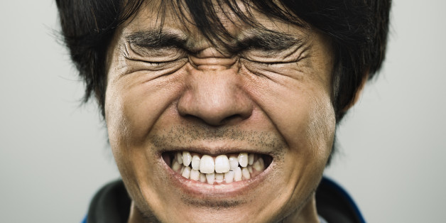 Studio portrait of a japanese young man with closed eyes and clenched teeth. The man has around 30 years and has long black hair and casual clothes. Vertical color image from a medium format digital camera. Sharp focus on eyes.