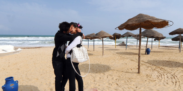 A young Tunisian couple kiss on the empty beach of Hammamet as thousands of Tunisian tour operators and residents of tourist town of Hammamet on April 23, 2011  march under the name 'citizen walk in support of tourism ' . AFP PHOTO FETHI BELAID (Photo credit should read FETHI BELAID/AFP/Getty Images)