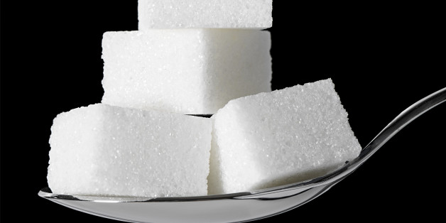 Sugar cubes stacked up on a teaspoon.  Black background.