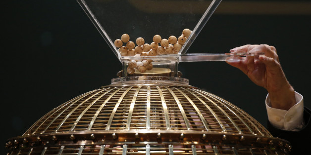 """A man puts the balls into the lottery drum before the draw for Spain's Christmas Lottery """"El Gordo"""" in Madrid December 22, 2014. The total prize money of 2.4 billion euros is split into thousands of cash prizes amongst hundreds of winning numbers. REUTERS/Juan Medina (SPAIN - Tags: SOCIETY)"""