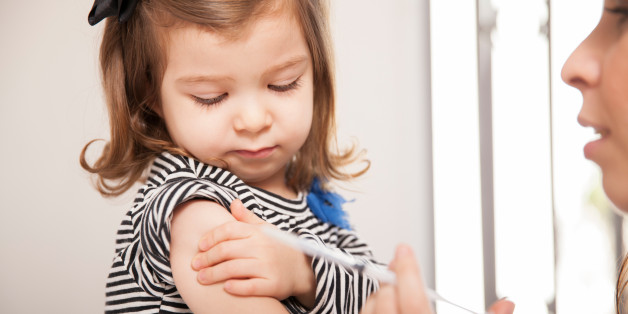 Closeup of a cute little girl getting a flu shot at a doctor's office