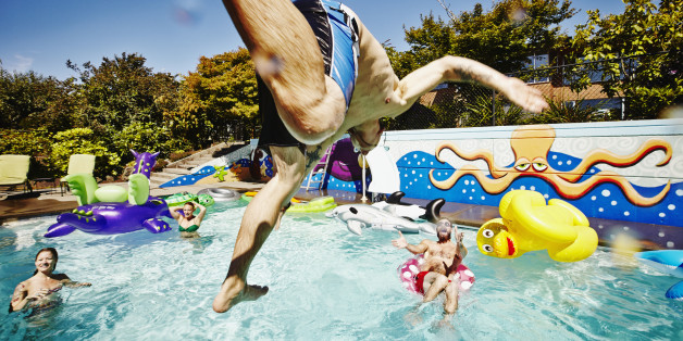 Man in mid air jumping into outdoor pool during party with friends swimming and cheering in background