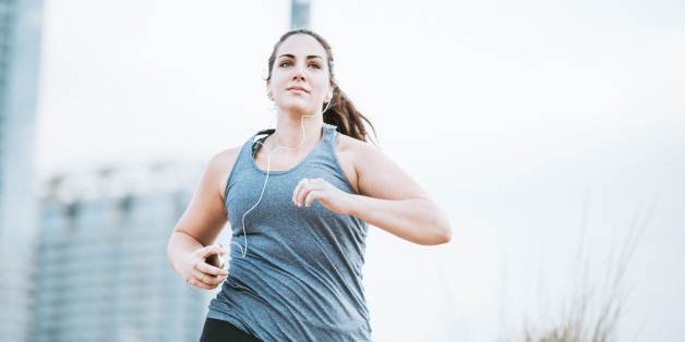 A young adult woman goes for a morning run, crossing the Lamar Street pedestrian bridge in Austin, Texas.  The bridge gets a large volume of foot traffic in the morning with people exercising at the start of their day.  She has a focused look of determination, listening to music on her smartphone.