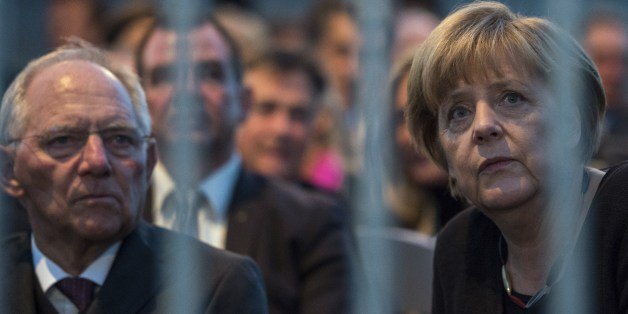German Chancellor Angela Merkel (R) and German Finance Minister Wolfgang Schaeuble wait for the start of a concert during celebrations of the Day of the German reunification (Tag der Deutschen Einheit) in front of the Reichstag building, seat of the German lower house of Parliament (Bundestag), in Berlin on October 3, 2015. Germany's political leaders celebrate the country's 25th anniversary since the reunification of East and West Germany.  AFP PHOTO / JOHN MACDOUGALL        (Photo credit shoul