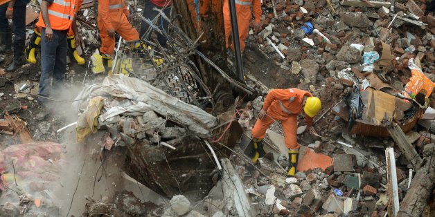 Indian rescue workers and fire officials look for survivors in debris at the site of a building collapse  in Mumbai on July 25, 2017. Rescuers were frantically searching for up to 40 people feared trapped in a four-storey building that collapsed July 25 in India's financial capital of Mumbai, officials said. / AFP PHOTO / PUNIT PARANJPE        (Photo credit should read PUNIT PARANJPE/AFP/Getty Images)