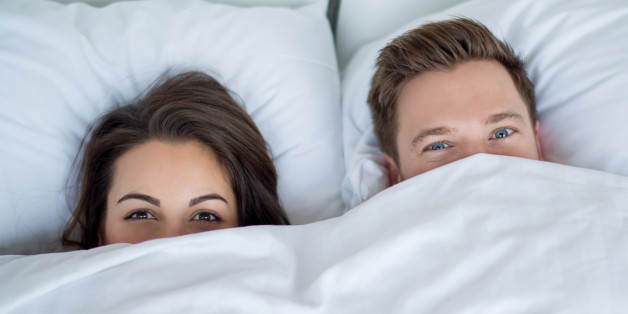 Young couple in bed covering with the sheets