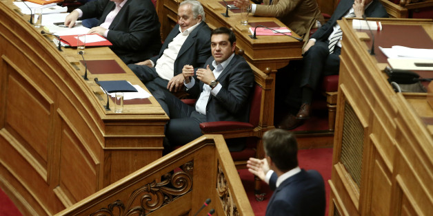 Greek PM Alexis Tsipras (C) gestures listening main opposition leader Kyriakos Mitsotakis delivering a speech on the podium, during a debate on education in the Greek Parliament, in Athens on September 28 , 2016 (Photo by Panayiotis Tzamaros/NurPhoto via Getty Images)