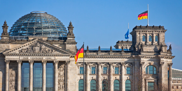 Flags of Federal Republic of Germany waving in front of the German parliament building (Reichstag) in Berlin, Germany