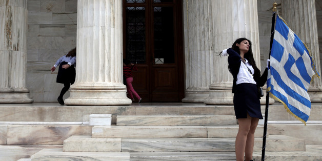 "Children (L) play hide and seek as a student holds a Greek national flag at the entrance of the Athens Academy, following a student parade marking the ""Ohi"" (No) day, the country's rejection on Italy's ultimatum to surrender as the World War II flared up, in Athens, Greece, October 28, 2016. REUTERS/Alkis Konstantinidis"