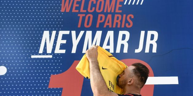 A PSG fan kisses a PSG yellow away jersey, marked with the number 10 and the name of Brazilian star Neymar, after he purchased it from the Paris-Saint-Germain (PSG) football club store on the Champs Elysees avenue in Paris on August 4, 2017.Brazilian superstar Neymar was expected in the French capital early Friday, promising to bring glory to Paris Saint-Germain after signing a world record transfer deal with the ambitious Qatari-owned club. / AFP PHOTO / PHILIPPE LOPEZ / ALTERNATIVE CROP