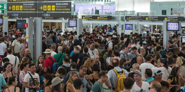 Passengers gather as they wait for passing the security controls at Barcelona's El Prat airport due to a strike of security agents on August 4, 2017, in Barcelona.As the tourism season in Barcelona is at its peak, security agents at the popular Mediterranean city's El Prat airport will go on strike from today in what could considerably lengthen queues for visitors. / AFP PHOTO / Josep LAGO        (Photo credit should read JOSEP LAGO/AFP/Getty Images)