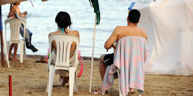 A Tunisian couple sits on the beach in  la Goulette city  on July 11, 2012 in Tunis as temperatures reached over 45 degreees Celcius over the week in Tunisia. Women and girls who used to swim in bikinis are scarce. Fearing possible attacks by organized religious extremists, they avoid these beaches. AFP PHOTO : FETHI BELAID        (Photo credit should read FETHI BELAID/AFP/GettyImages)