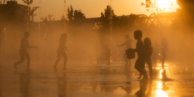 Madrid, Spain - July 12, 2013: Young kids scape from the summer heat wave at dusk playing with the water jets in the fountains of the recently renovated Madrid RA-o park, by the Manzanares River in Madrid, Spain.