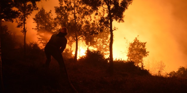 IZMIR, TURKEY - JULY 25: A member of fire department tries to extinguish a forest fire in Bayindir district of Izmir, Turkey on July 25, 2017. Approximately 300 hectare forestland is affected by the fire. (Photo by Haluk Satir/Anadolu Agency/Getty Images)