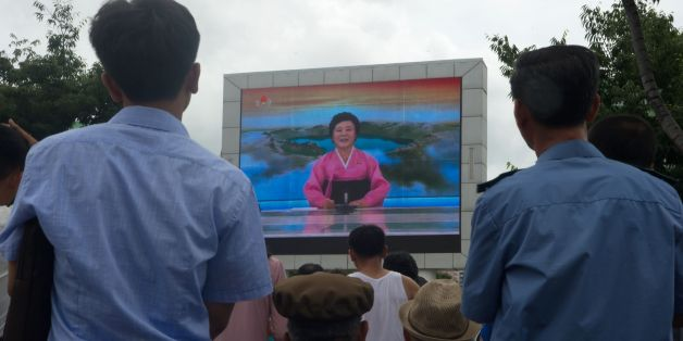 People watch as coverage relating to an ICBM missile test is displayed on a screen in a public square in Pyongyang on July 29, 2017.