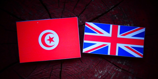 Tunisian flag with UK flag on a tree stump isolated