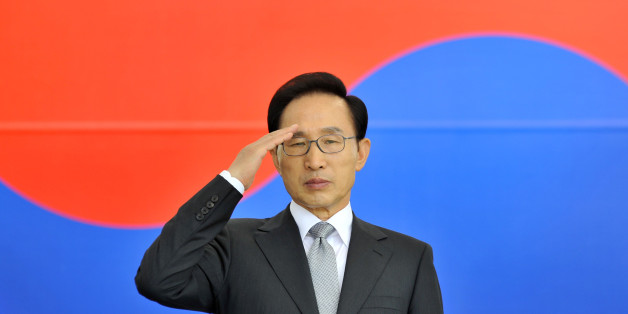 South Korean President Lee Myung-Bak salutes in front of the national flag during a ceremony to mark the 64th Korea Armed Forces Day, which will fall on October 1, at the military headquarters in Gyeryong, about 140 kms south of Seoul, on September 26, 2012. Lee called for building stronger armed forces saying North Korea keeps posing missile and nuclear threats, and regional tensions are escalating over history and sovereignty issues.    AFP PHOTO / POOL / JUNG YEON-JE        (Photo credit shou