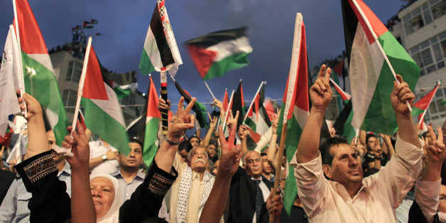 Palestinians gesture and wave flags before a public screening of Palestinian President Mahmoud Abbas' speech at the United Nations, in the West Bank city of Ramallah September 23, 2011. Abbas asked the United Nations on Friday to recognize a state for his people, even though Israel still occupies its territory and the United States has vowed to veto the move. REUTERS/Darren Whiteside (WEST BANK - Tags: POLITICS)