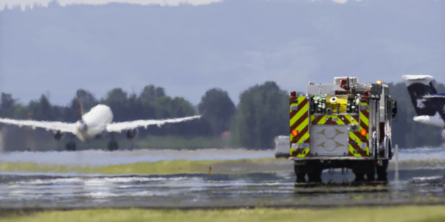 Aircraft taking off with firetruck on runway