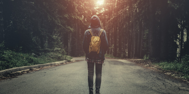 Tourist with backpack walking in a foggy forest at sunset. Stock photo.