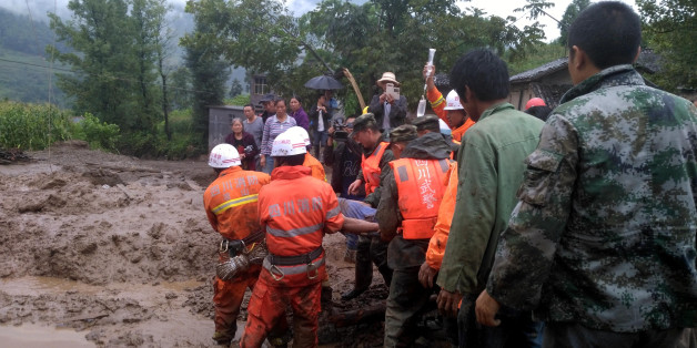 Rescuers carry a survivor at the site of a landslide in Puge in China's southwestern Sichuan province on August 8, 2017. A landslide triggered by heavy rain killed 8 people and left 17 others missing. / AFP PHOTO / STR / China OUT        (Photo credit should read STR/AFP/Getty Images)